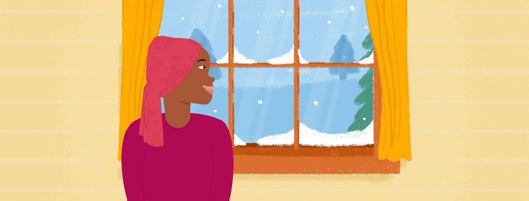 A woman looking out the window at a snowstorm