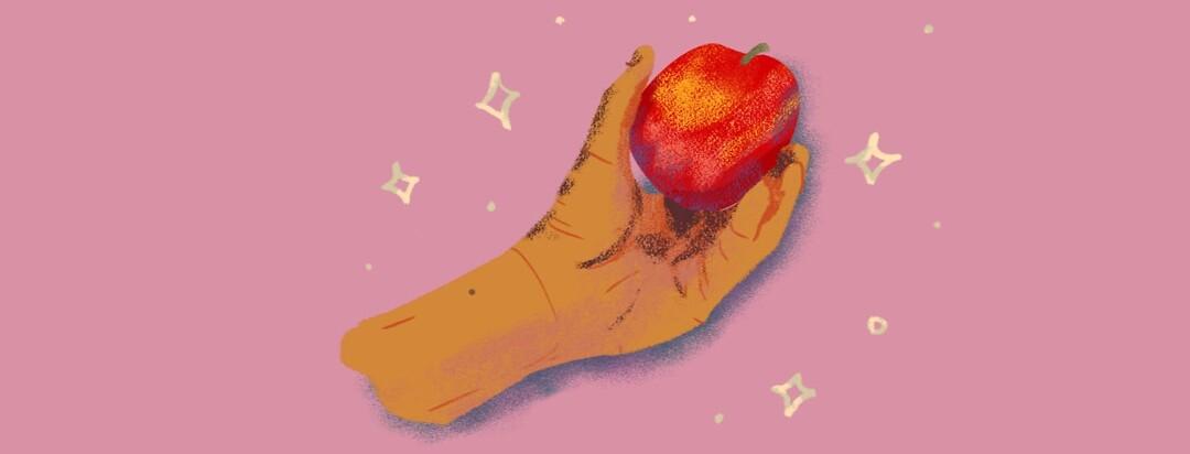 a hand holding an apple